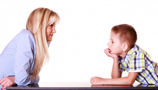 Mother and son talk and argue sit at table.
