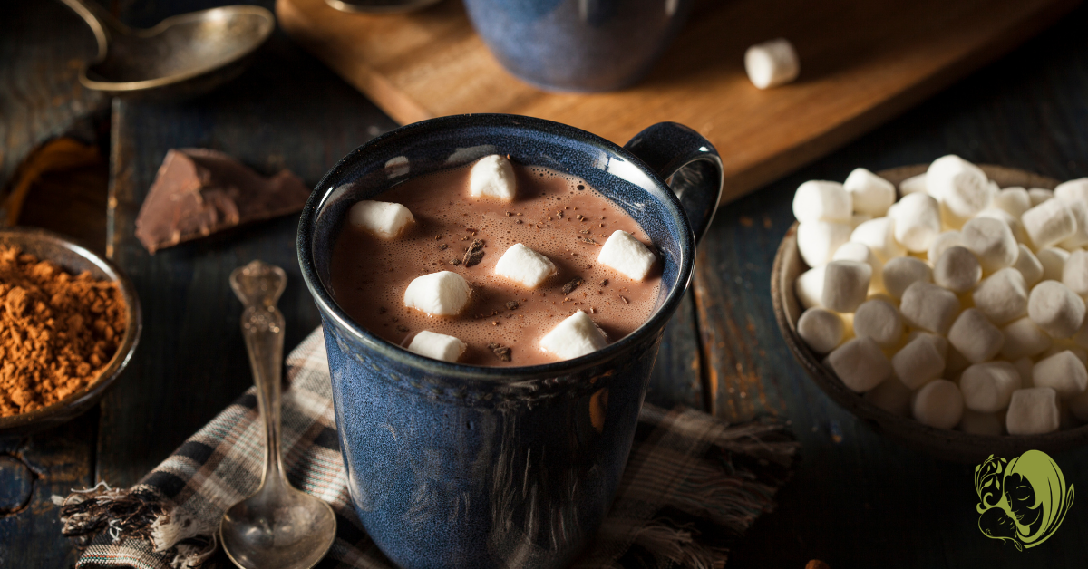 Cup of hot cocoa with marshmallows and other toppings surrounding.