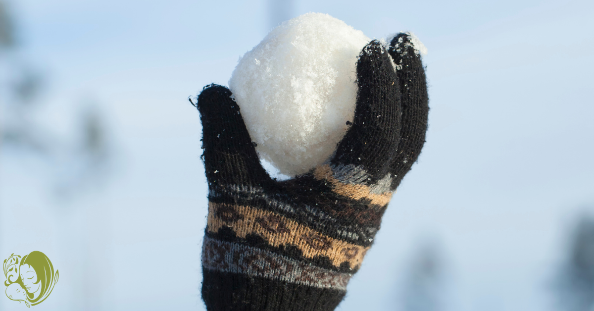 Kid holding snowball as one of the ways to enjoy the snow with your kids.